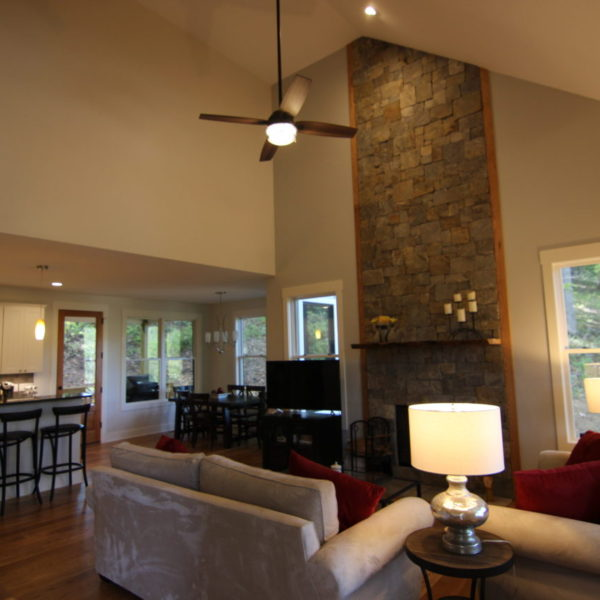 Living room with stone fireplace and open floor plan including kitchen and dining room
