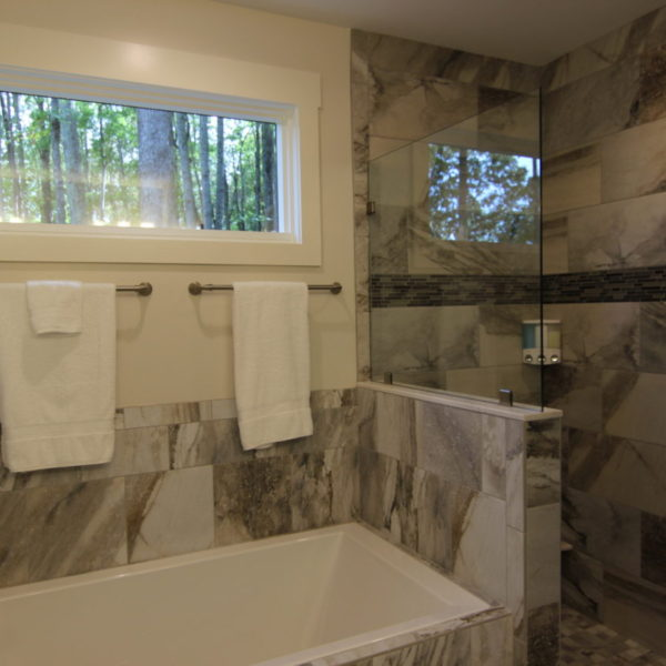 Master modern bathroom with large marble tiles in both bathtub and shower
