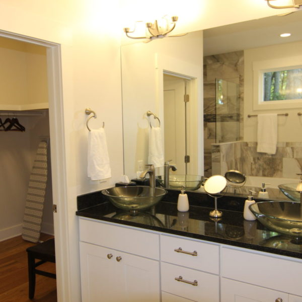 Modern guest bathroom with large marble tile flooring and glass double sinks