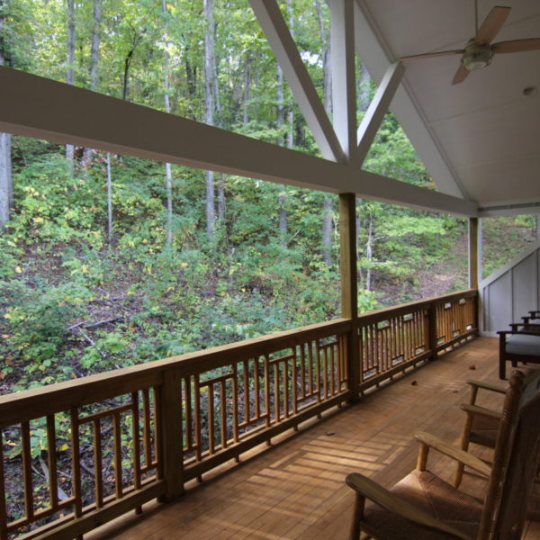 Long wooden rear upper porch with forest view