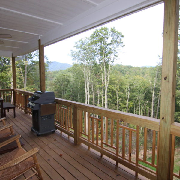 Rear large wooden porch with chairs and grill
