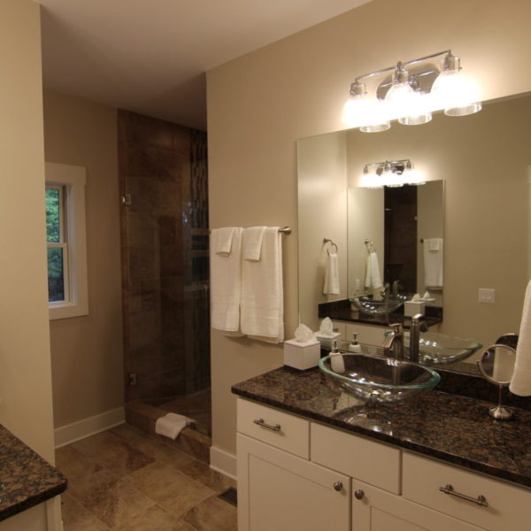 Upper modern bathroom with two glass sinks and glass shower
