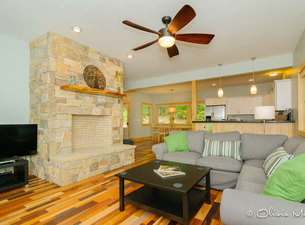 Living room with multicolored hardwood floors and stone masonry fireplace