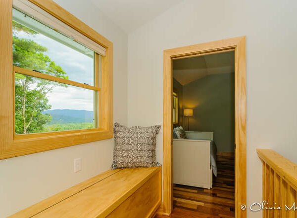 Reading nook with wooden seat by window with mountain views