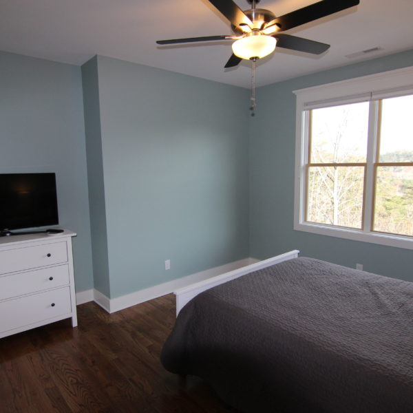 Third modern bedroom with light blue walls and white accent furniture